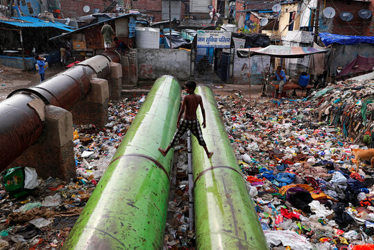 Boy stands on water pipes over a drain covered with garbage at a slum area on World Environment Day in New Delhi