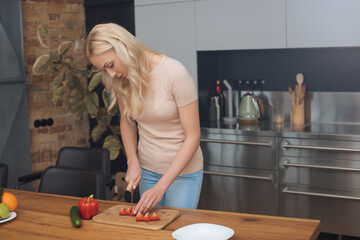 young blonde woman cutting fresh vegetables while cooking in modern kitchen