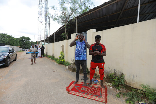 Two men pray outside a mosque, as places of worship reopen after the relaxation of restrictions imposed to curb the spread of the coronavirus disease (COVID-19) in Abuja