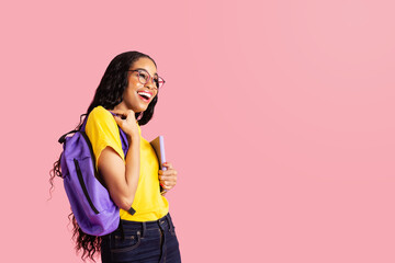 Portrait of a  laughing  young female student with book, backpack and glasses ready for school looking at  pink studio copy space