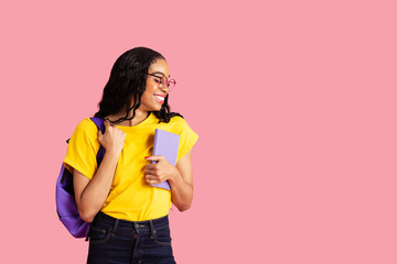 Portrait of a friendly young female student with book, backpack and glasses ready for school looking to side at pink studio copy space