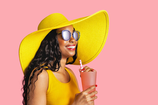 Profile portrait of a young smiling woman with yellow summer hat and sunglasses holding a drinking cup and paper straw