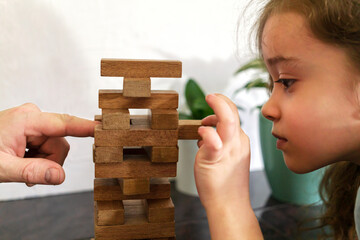 Father and daughter playing game Tumble tower from wooden block together