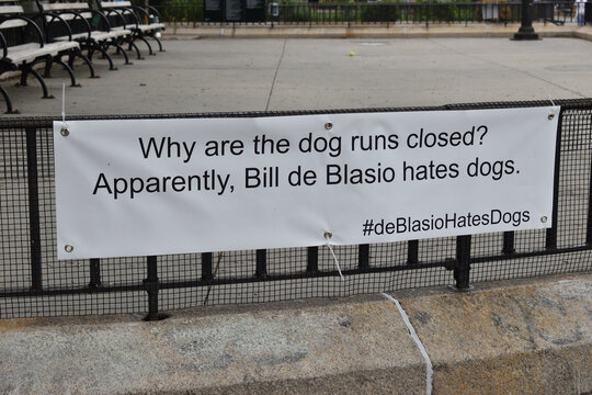 """Banner reading """"Why are the dog runs closed? Apparently, Bill de Blasio hates dogs - #deBlasioHatesDogs"""" on the fence of a dog run in a public park, June 5, 2020, in New York."""