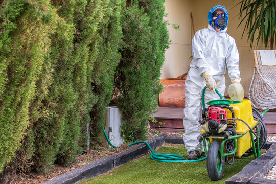 Fumigator with a motorized fumigation machine preparing fungicide and phytosanitary products for pest control and fertilizer of plants. The fumigator is wearing a protective suit against toxic product