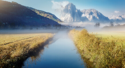 Fotomurales - Wonderful picturesque Scene. Amazing Misty Morning. Beautiful nature Scenery. scenic view of Majestic Mountain Peak with river foreground, shoot in morning in Autumn season, Fantastic Alpine Landscape