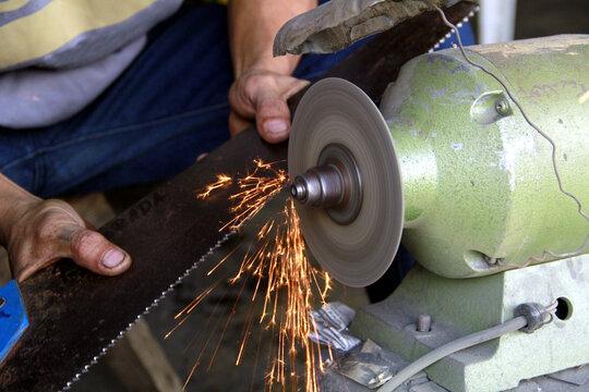 Blacksmith's hands sharpening a carpenter's saw using a bench grinder