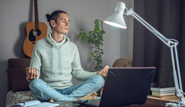 Employee is meditating in the Lotus position while working hard remotely at home. Calm and serenity during a crisis