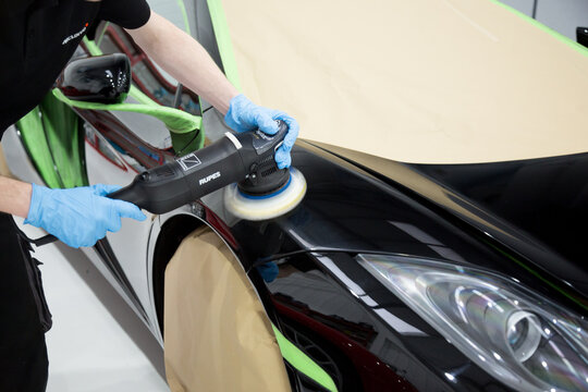 Detailer using a rotary machine on a sports car panel on January 9, 2017 in London, U.K.