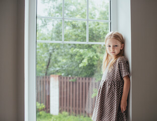girl in a polka dot dress looking by the window