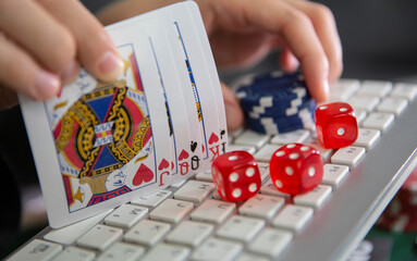 Keyboard, cards, chips, dice are seen in this illustration picture