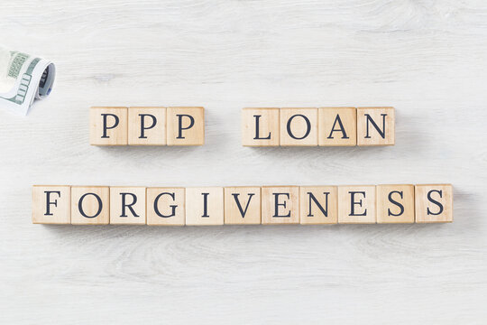 PPP LOAN FORGIVENESS text on wooden blocks on grey wooden background. US dollars roll. Small business Paycheck Protection Program. Banking and finance concept