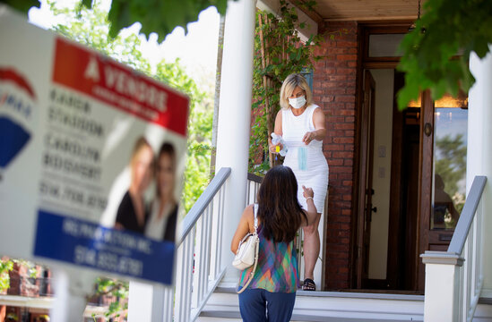 Real estate agent Karen Staddon hands out a mask to a client visiting a home for sale amid the coronavirus disease (COVID-19) outbreak in Montreal