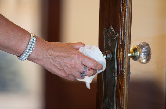 A real estate agent disinfects a door handle with wipes during a client's visit to a home for sale, amid the coronavirus disease (COVID-19) outbreak, in Montreal