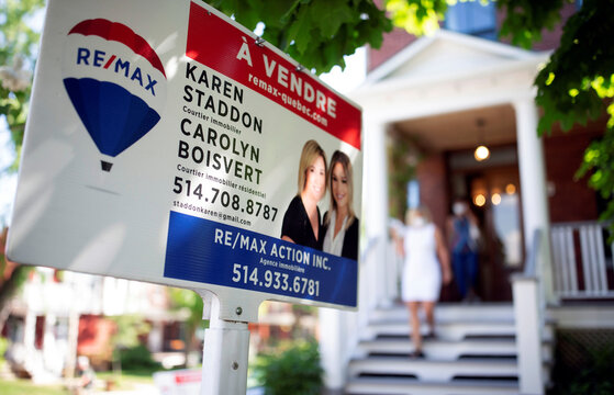 A view shows a sign of a house for sale as a real estate agent shows it to a client, amid the coronavirus disease (COVID-19) outbreak, in Montreal