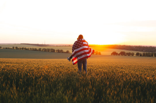Image of  young couple with the American flag in a wheat field at sunset.  Independence Day, 4th of July.