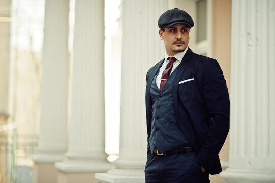 Portrait of retro 1920s english arabian business man wearing dark suit, tie and flat cap.