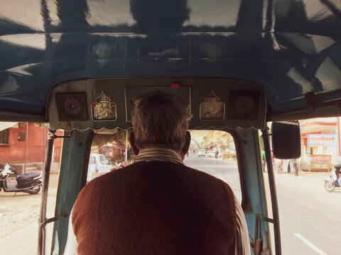 Back view of an old man driving a tuk tuk taxi in the streets of Nepal