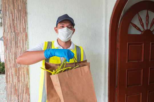 A messenger with a protective medical mask and gloves holding bags full of different foods. Home service during the pandemic. Online food ordering, delivery during quarantine, coronavirus outbreak