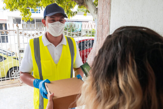 A delivery man with a mask and gloves delivers a box. The customer receives the order from a courier at home, fresh organic food online
