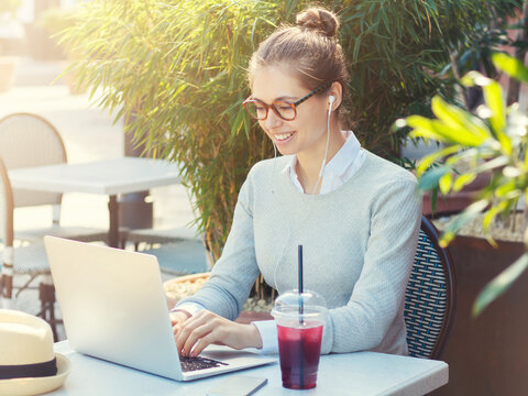 Outdoor portrait of young smiling woman sitting at cafe table surrounded by greenery, her laptop open, listening to music through earphones, drinking smoothie and enjoying summer time outside