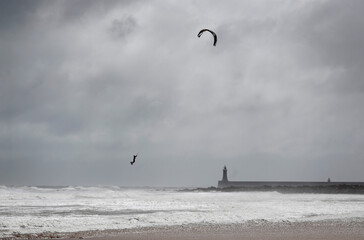 A man is seen kite surfing in windy weather over the sea at Tynemouth
