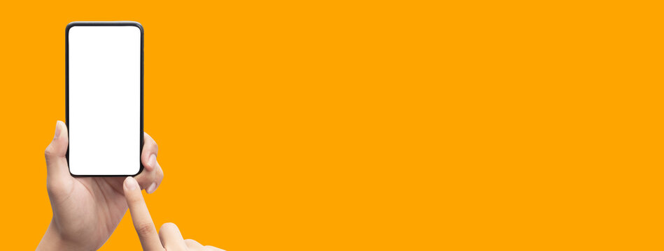 Hand holding the black smartphone and touching blank screen on colorful orange banner background, Clipping path.