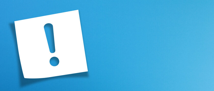 Note paper with exclamation mark on panoramic blue background