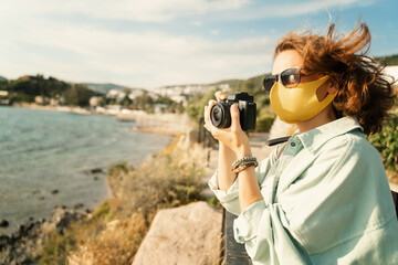 Cool beautiful happy girl woman traveler by the sea with a mask on her face, stylish outfit, with a...