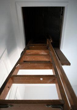Steep old stairs leading to a dark hole in the attic