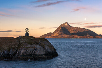The Arctic Circle marker at 66° 33' North on the little island of Vikingen, with the mountain of Hestmonkallen on the island of Hestmona beyond: Rødøy, Nordland, Norway