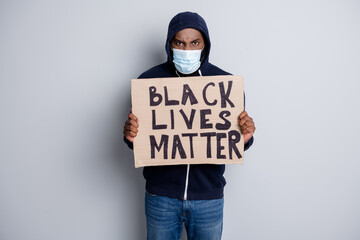 Save black lives. Photo of mad dark skin african poor covid infected protester hold placard stand against black citizens lawlessness wear hoodie face mask isolated grey color background