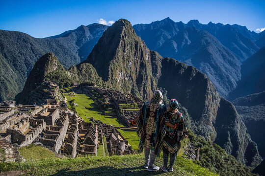 Couple watching the ruins of Machu Picchu in Peru