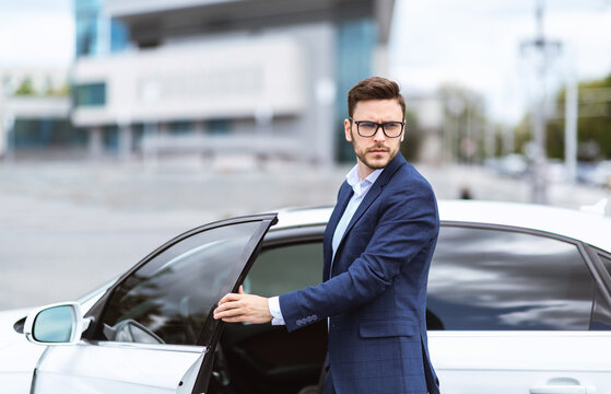 Successful banker near his car on street of megapolis