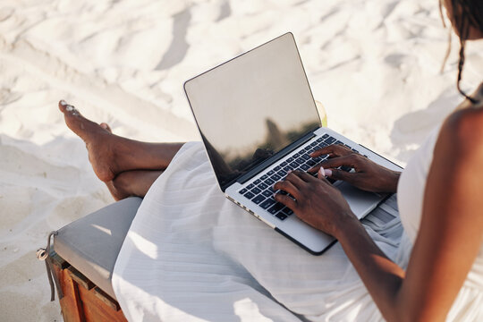 Young woman with laptop sitting on chaise-lounge on beach and working remotely