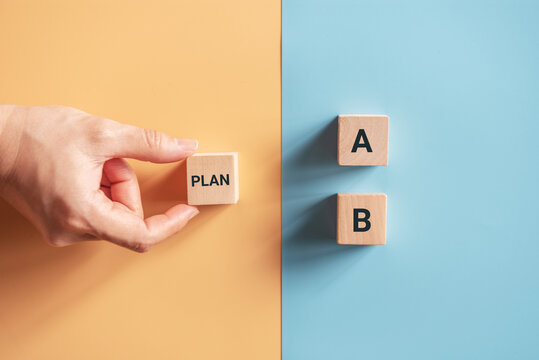 Hand choose wooden cube with the word PLAN A to PLAN B on blue and yellow background. Business concept.