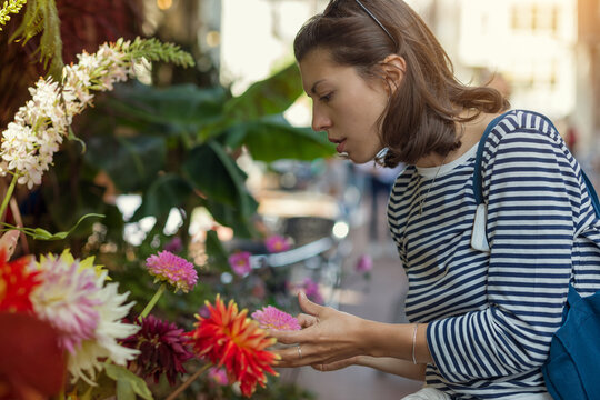 An attractive young woman picks flowers in an outdoor flower shop.