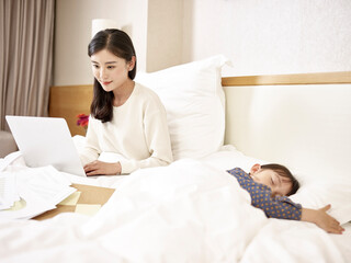 young asian mother working on bed with sleeping daughter by side