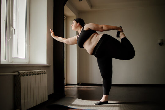 Overweight woman doing yoga exercise in living room. Yoga for weight loss, healthy lifestyle and home workout