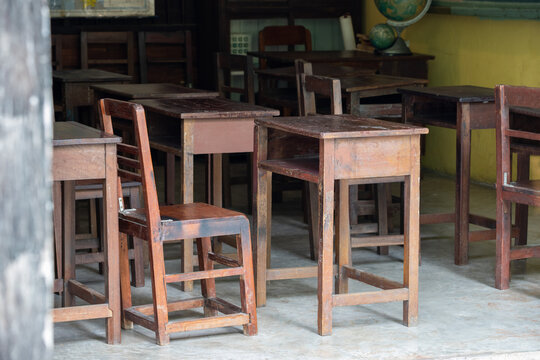 old wooden table for Thai student in urban school. dirty timber desk no student in classroom. Concept : shortage school equipment. school closure caused coronavirus or Coivd-19.