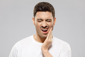 Young guy with closed eyes suffering from severe toothache, touching jaw with fingers trying to ease strong tooth pain, isolated on gray background