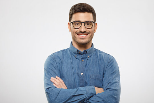 Young business guy wearing blue shirt and eyeglasses, standing with arms crossed, smiling happily and feeling confident, isolated on gray background