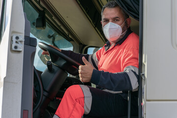 Truck driver with face mask in the cockpit making the ok sign