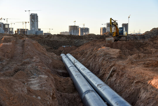 Excavator during construction of main water supply pipeline. Laying underground storm sewers at construction site. Water main sanitary drainage system for a multi-story buildings
