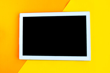 Tablet with black mockup screen on orange geometric background. Copy space for the text. Minimal...
