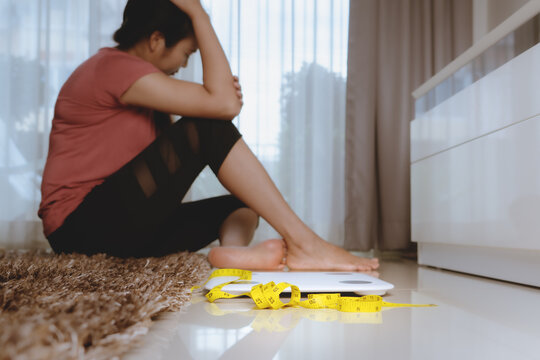Weight loss fail concept. Scale and measure tape with depressed, frustrated and sad woman sitting on floor