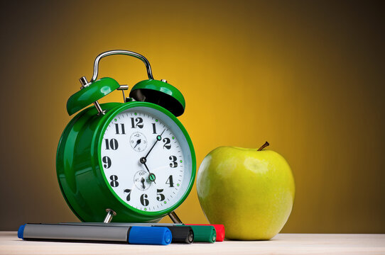 Green alarm clock, markers and apple on yellow background