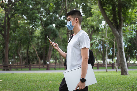 asian young man wearing mask is using phone for social media in nature park.male student is holding laptop while stay alone in garden for keep social distancing in summer due to quarantine time.