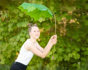 Fotomontage - junges, kaukasisches Mädchen schützt sich mit einem übergroßen Ahornblatt vor Regen und Sonne