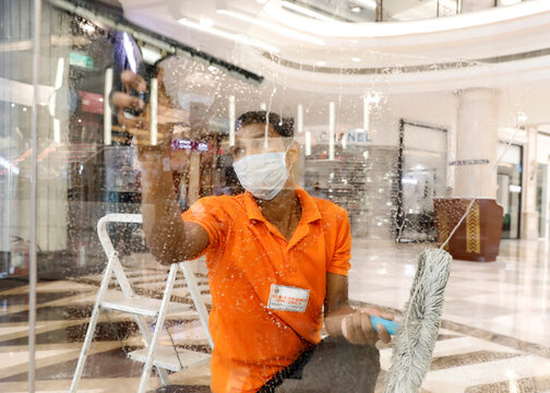 A worker cleans a window of a shop at a mall ahead of its reopening during an extended nationwide lockdown to slow down the spread of the coronavirus disease (COVID-19), in New Delhi